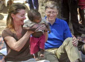 In this Wednesday, March 23, 2011 photo Microsoft Corp. founder and philanthropist Bill Gates, right, and his wife Melinda Gates attend to a child as they meet with members of the Mushar community at Jamsot Village near Patna, India. (AP Photo/Aftab Alam Siddiqui)